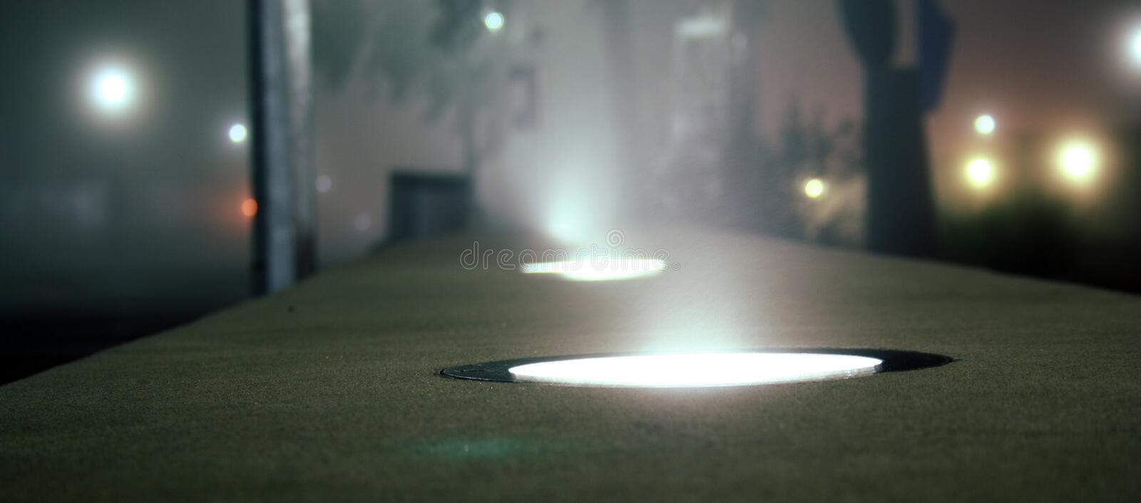 Ground light source. A ground light source illuminating during a foggy evening royalty free stock photo