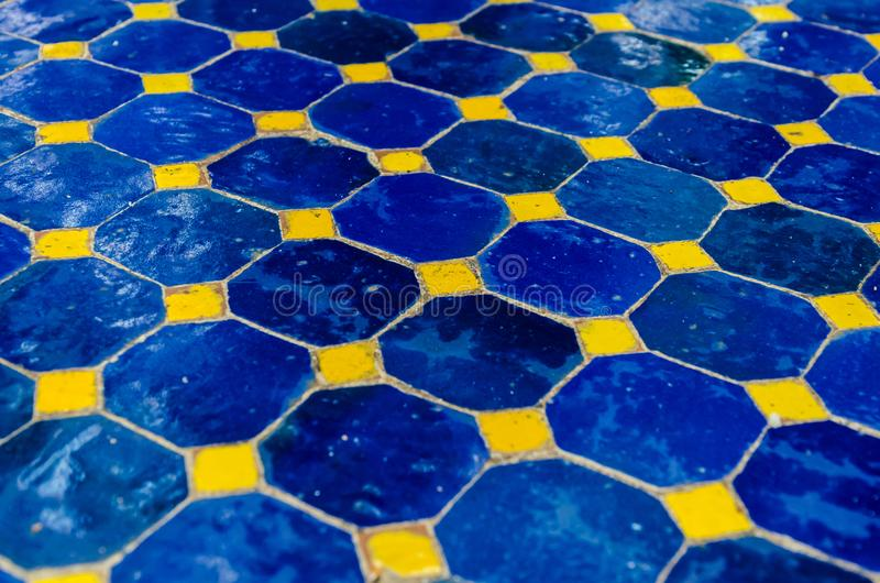 Ground made with ceramic tiles in blue and yellow. Detail on a floor made with ceramic tiles in blue and yellow stock photography