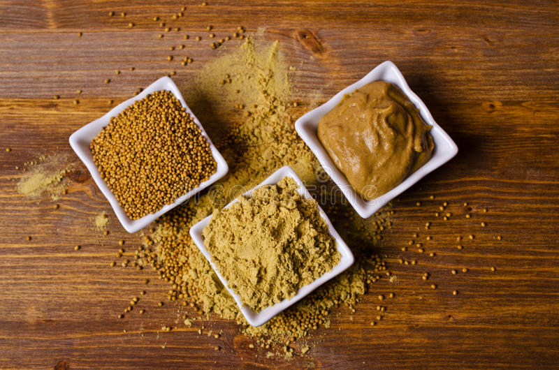 Ground mustard powder. On a wooden background. Selective focus royalty free stock photography