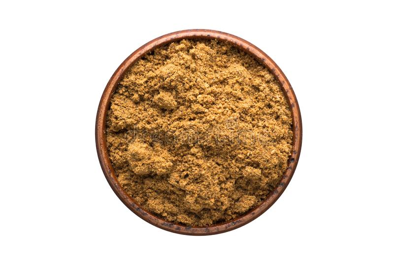 Ground nutmeg powder spice in wooden bowl, isolated on white background. Seasoning top view. Ground nutmeg powder seasoning in a wooden bowl, top view. spice royalty free stock images