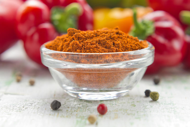 Ground paprika. In a white china bowl and fresh pepper royalty free stock images