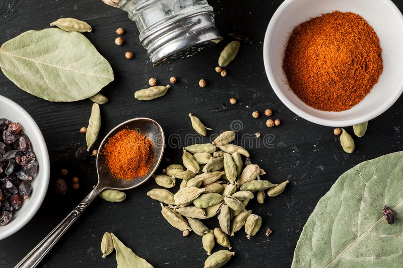 Ground paprika, cardamon seeds and other condiments on a black wooden table, top view, flat lay composition stock images