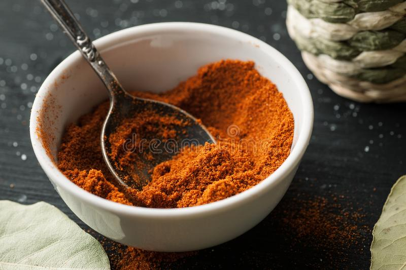 Ground paprika powder in a white ceramic bowl with metal spoon in it, closeup shot. Food, black, dried, kitchen, spices, view, dry, heap, herb, horizontal royalty free stock image