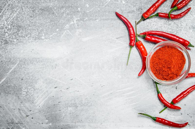 Ground pepper in a glass bowl and fresh red pepper with rosemary. On rustic background royalty free stock photo