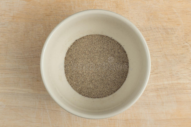 Ground pepper. Isolated a bowl of ground pepper on the wood block royalty free stock image