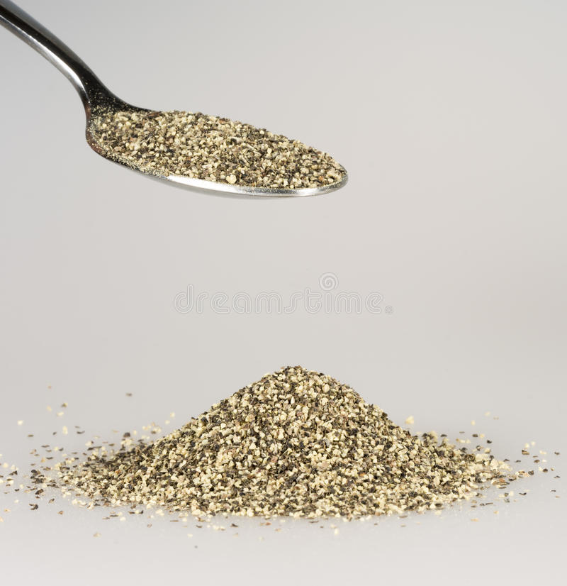 Ground Pepper on Tablespoon. With a pile of black pepper beneath royalty free stock photos