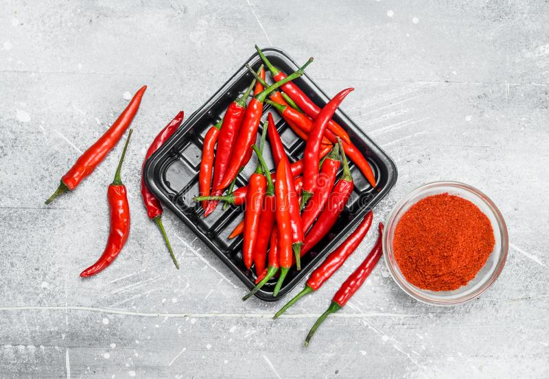 Ground red pepper in a bowl and the peppers on the tray. On rustic background royalty free stock images