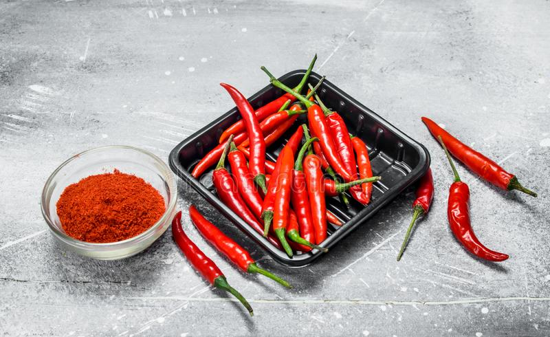 Ground red pepper in a bowl and the peppers on the tray. On rustic background stock photo