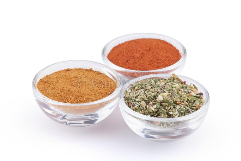 Ground red pepper, paprika and italian herbs in glass bowls isolated on white background royalty free stock photo