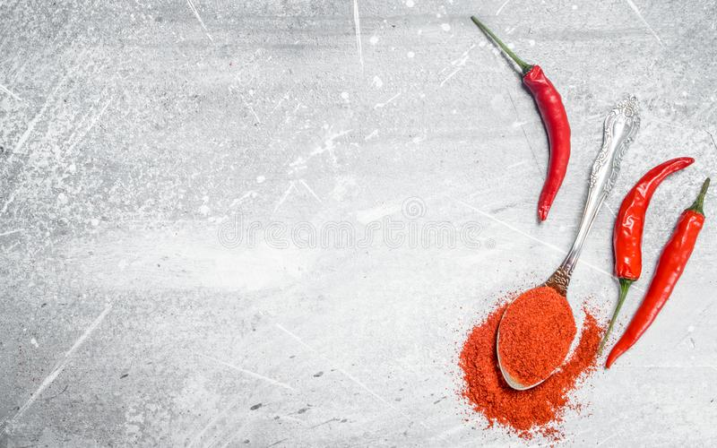 Ground red pepper in a spoon with fresh pepper pods stock photography