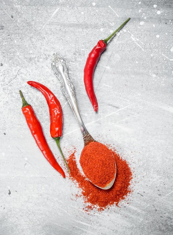 Ground red pepper in a spoon with fresh pepper pods. On rustic background royalty free stock image