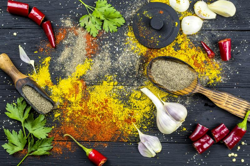 Ground spices, garlic and pepper on black wooden background stock photography