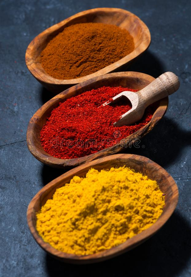 Ground spicy paprika, turmeric and red pepper in a wooden bowl, vertical top view. Ground spicy paprika, turmeric and red pepper in a wooden bowl, top view royalty free stock image