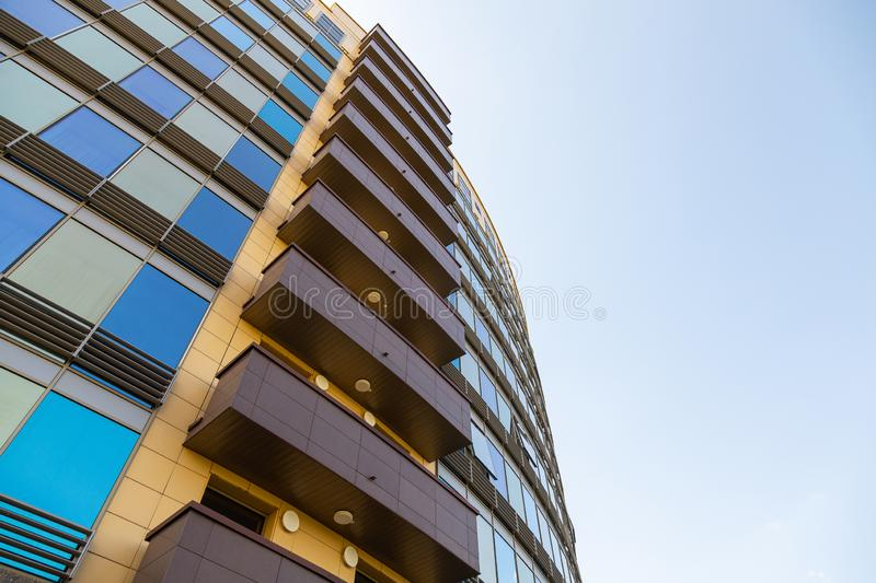 Ground view of blue and golden glass surface of building wall with windows and brown balconies. Bottom view of blue and golden glass surface of building wall royalty free stock image