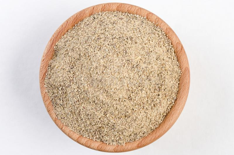 Ground white pepper in wooden bowl isolated on white background.  stock image