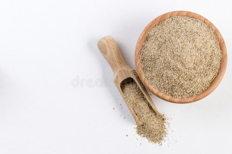 Ground white pepper in wooden bowl and scoop isolated on white background with copy space added. top view.  stock photo
