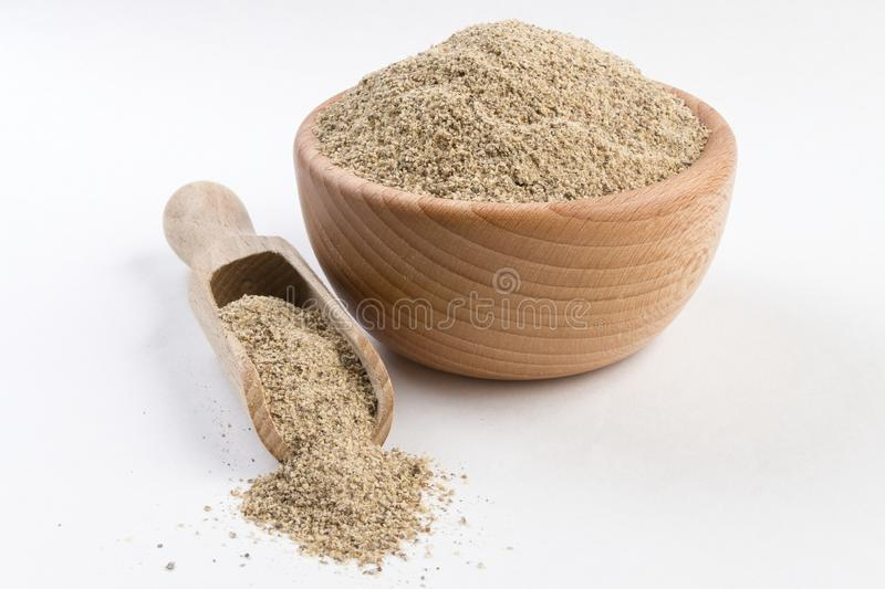 Ground white pepper in wooden bowl and scoop isolated on white background.  royalty free stock photo