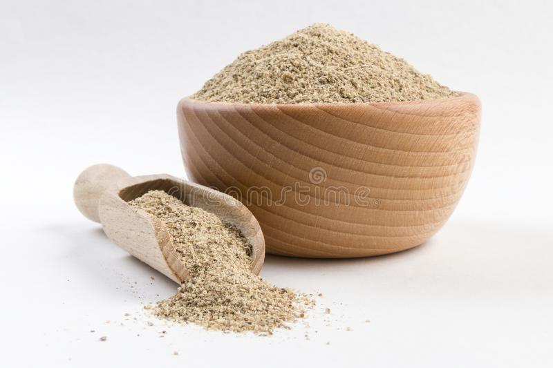 Ground white pepper in wooden bowl and scoop isolated on white background.  stock photos
