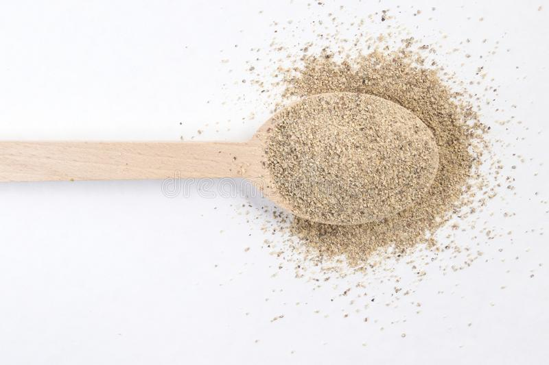 Ground white pepper in wooden spoon isolated on white background. top view.  stock image