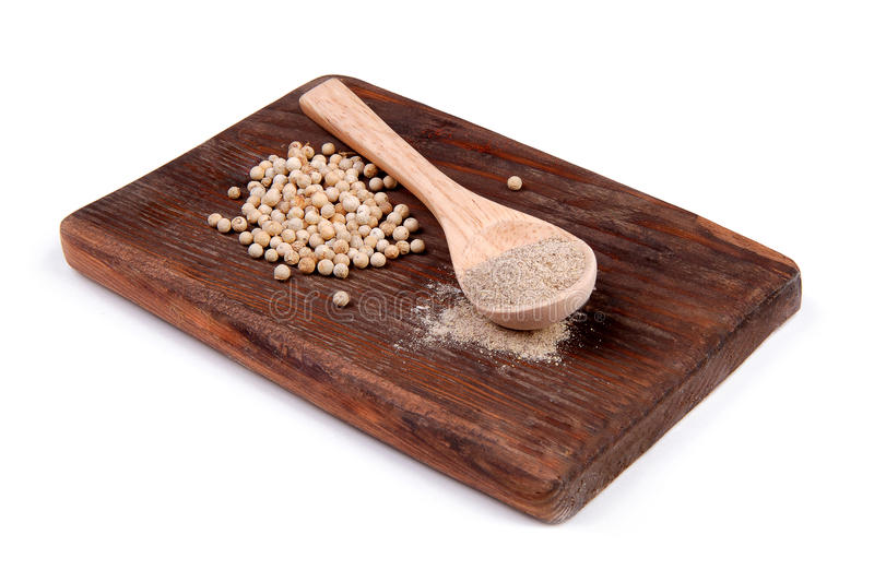 Ground white pepper in a wooden spoon on a wooden board. Ground white pepper and white pepper on a wooden board royalty free stock image