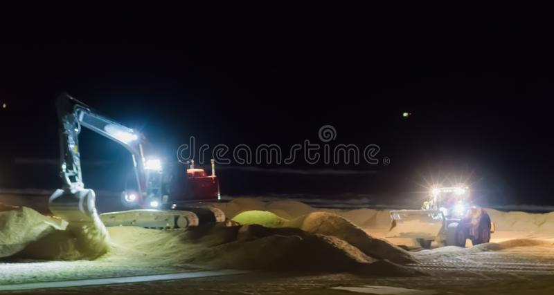 Ground workers working at night in a digger excavator and bulldozer moving the sand at the beach royalty free stock images
