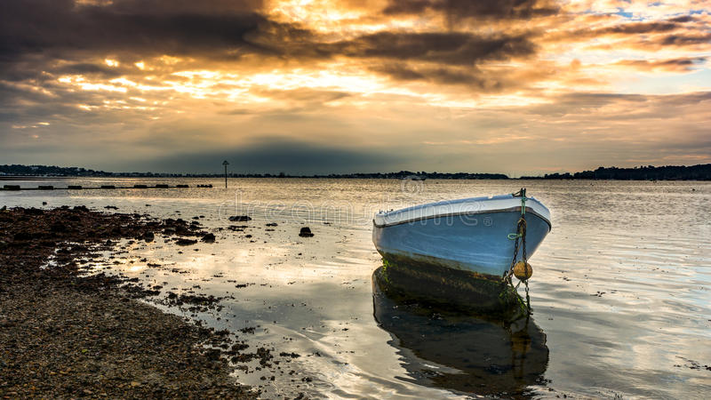 Grounded again. Taken at Baiter Beach Poole Dorset UK, at a low tide sunrise. The sun behind the clouds that morning gave a wonderful golden glow to the sea and royalty free stock photo