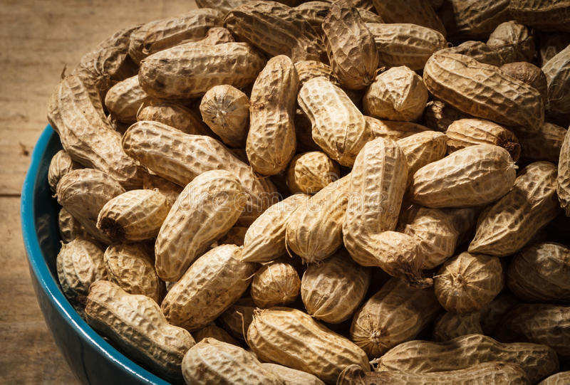 Groundnut. In blue bowl on wood background stock photos