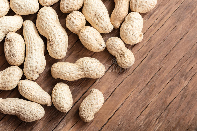 Groundnut in the skin close-up. On a wooden background stock photography