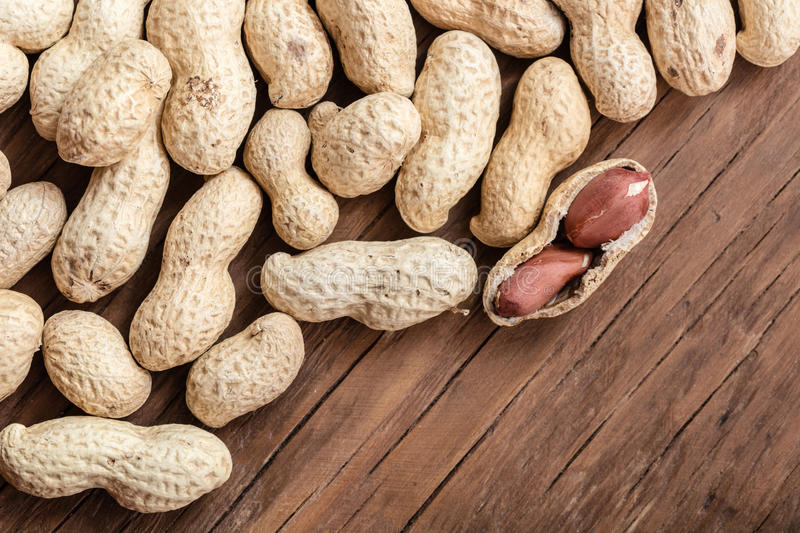 Groundnut in the skin close-up. On a wooden background stock photo