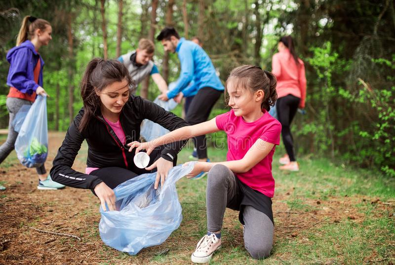Group of active people picking up litter in nature, a plogging concept. A roup of active young people picking up litter in nature, a plogging concept royalty free stock photo
