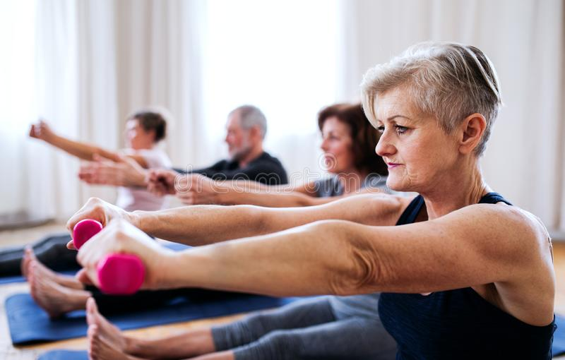 Group of senior people doing exercise with dumbbells in community center club. royalty free stock photos