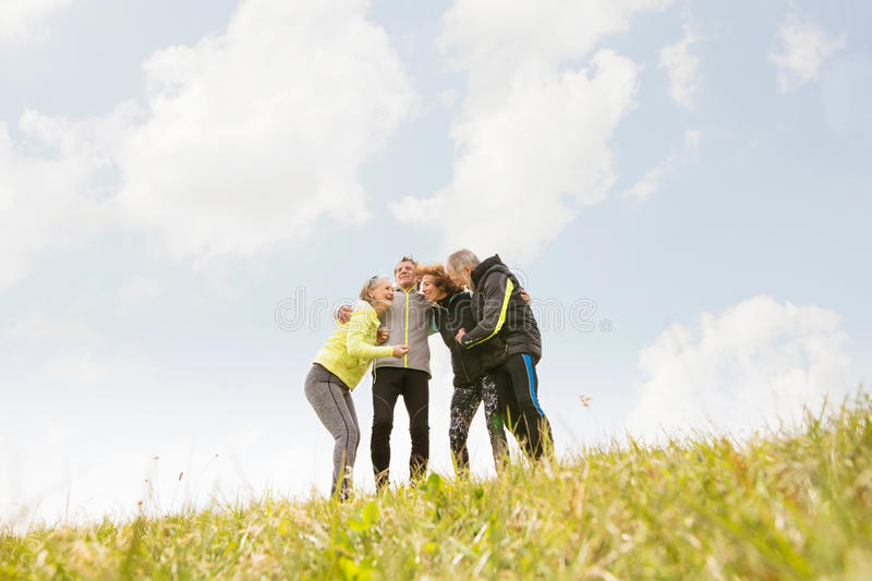 Group of senior runners outdoors, resting, holding around arms. stock photography