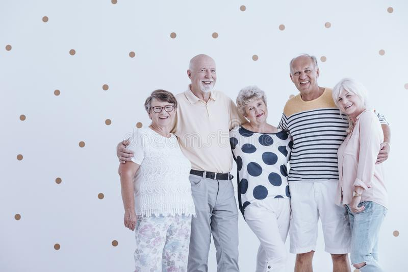 Group of active seniors. Posing for a photo against white wallpaper with gold dots stock photos