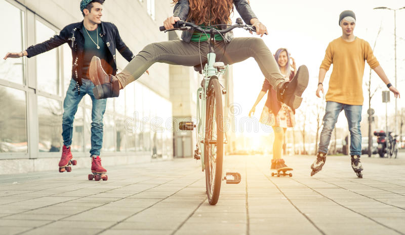 Group of active teenagers in town. four teens making recreational activity in an urban area royalty free stock photos