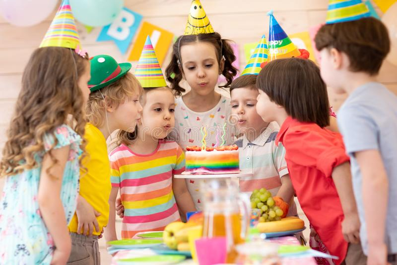 Group of adorable kids gathered around festival table. Children blow out candles on cake. Birthday party for. Group of adorable kids 3-5 years gathered around stock images
