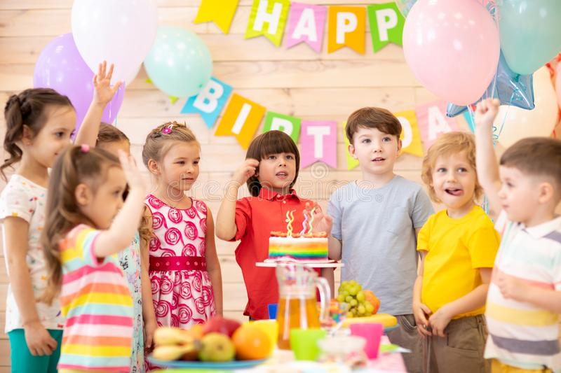 Group of adorable kids gathered around festive table. Birthday party for preschoolers royalty free stock image