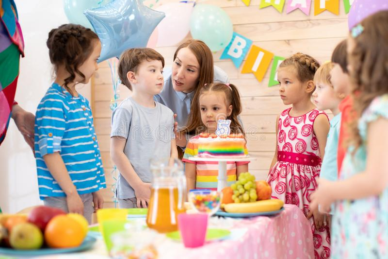 Group of adorable kids gathered around festive table. Birthday party for preschoolers stock photo
