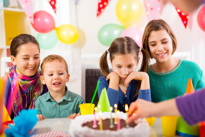 Group of adorable kids having fun at birthday party, selective focus royalty free stock photography