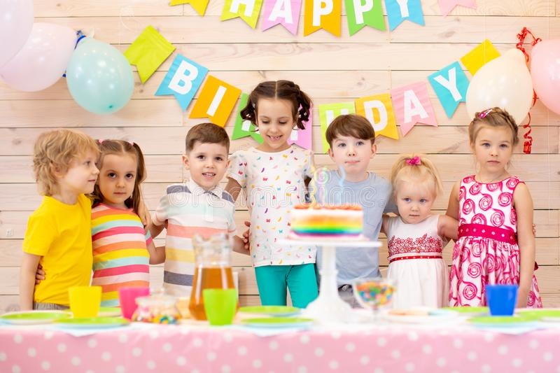 Group of adorable kids stand around festive table at birthday party stock images