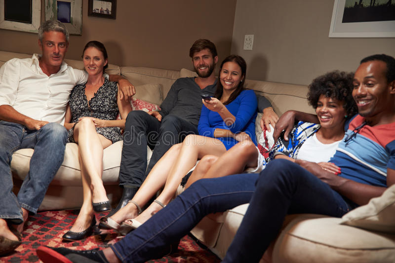 Group of adult friends watching television together royalty free stock images