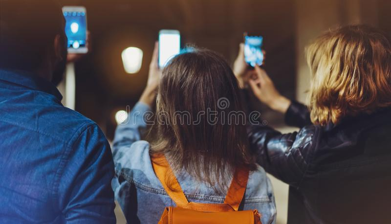 Group adult hipsters using in hands mobile phone closeup, online wi-fi internet concept in street, bloggers friends together. Pointing finger on screen stock image