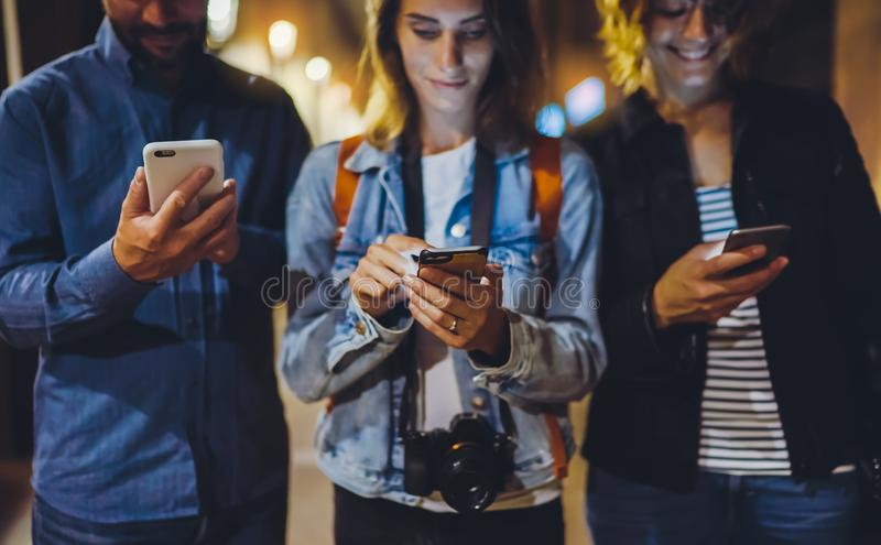 Group adult hipsters using in hands mobile phone closeup, street online wi-fi internet concept, bloggers friends together. Pointing finger on screen smartphone stock photos