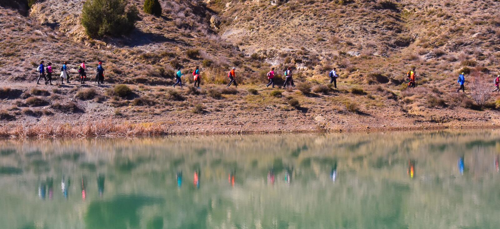group of adult people with colorful backpack trekking on a path of sand and stones walking next to a lake reflecting their images stock photos
