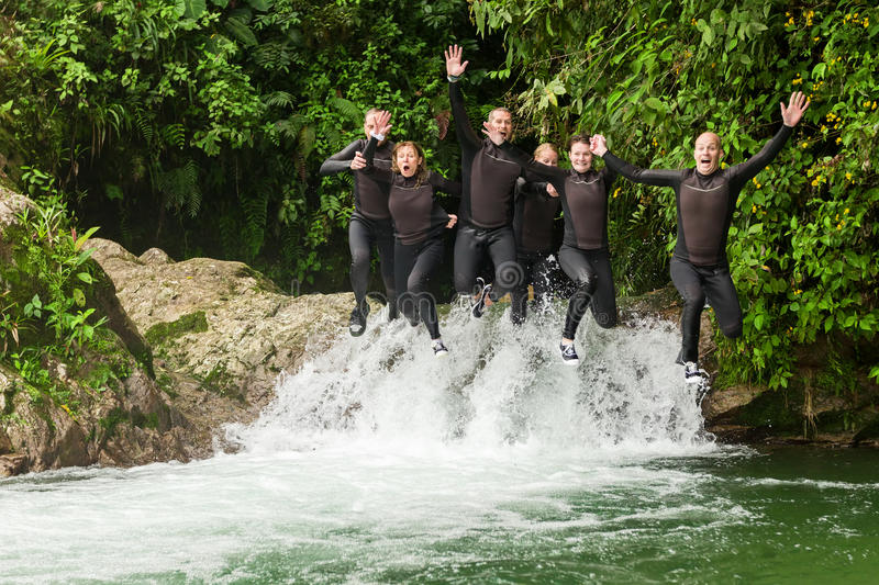 Group Of Adult People Jumping Into Small Waterfall stock photography