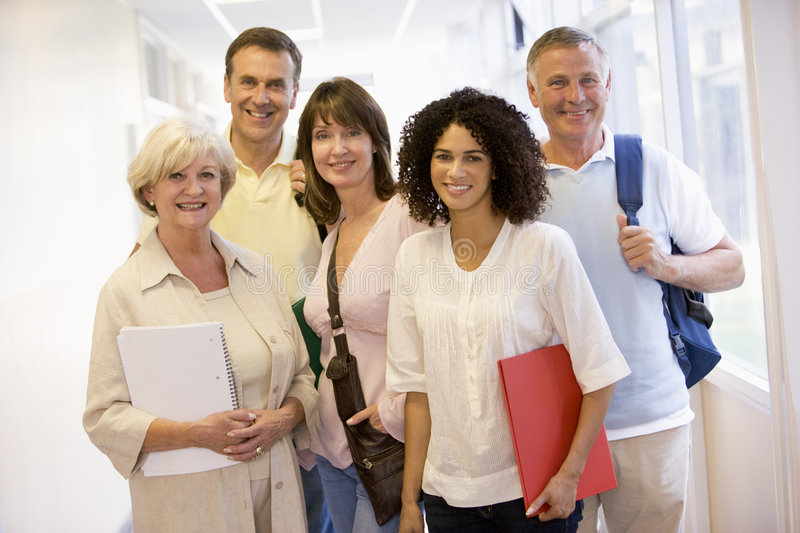 A group of adult students with backpacks standing stock photo