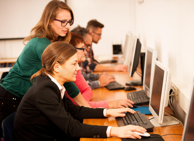 Group of adults learning computer skills. Intergenerational tran stock photos