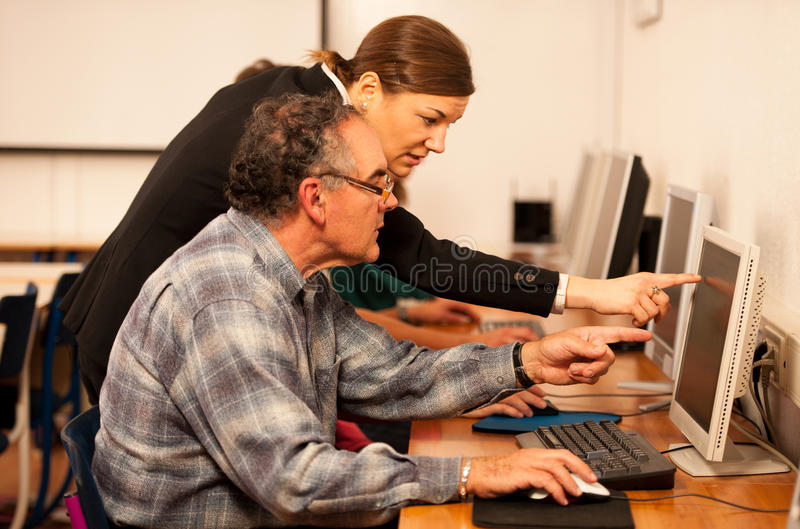 Group of adults learning computer skills. Intergenerational tran stock photography