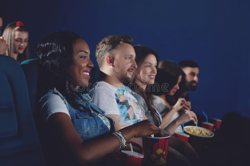 Group of african and caucasians watching movie in cinema. Side view of group of african girl and caucasians couple watching movie in modern cinema hall. Young royalty free stock photo