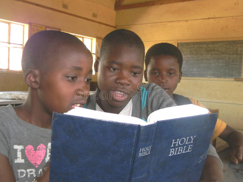 Group of African school kids reading Bible. Norton,Zimbabwe,July 7 2015.Three primary school pupils share a Bible inside their classroom at school.In sub stock photo