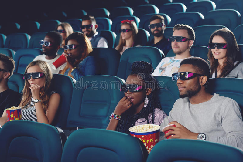 Group of africans and caucasians spending free time in cinema. Group of africans and caucasians watching movie in 3d glasses in modern cinema hall. Young people stock photo